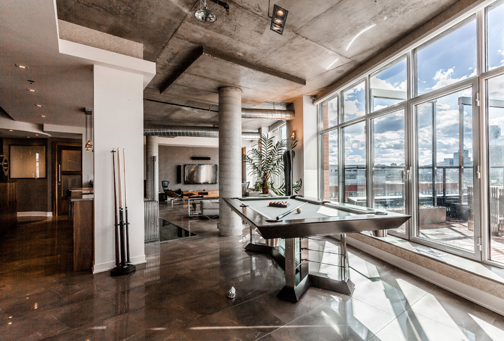 This Montreal penthouse has a games room specifically designed for entertaining; it boasts a pool table, full bar/kitchen, powder room, dinette, sauna, and home theater.