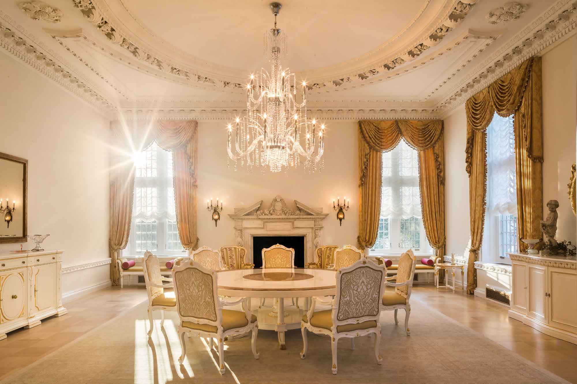 A crystal chandelier illuminates the beautifully appointed tea room, one of the mansion's grand reception rooms.