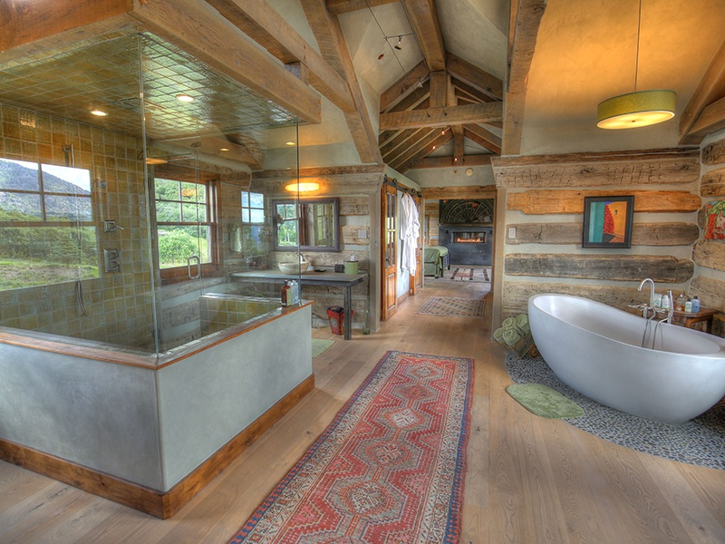 The spectacular guest wing of this Colorado home, currently being marketed by Telluride Real Estate Corp., an affiliate of Christie's International Real Estate, features a bath with vaulted ceilings, ash floors, a soaking tub, and a rain shower with wall jets.
