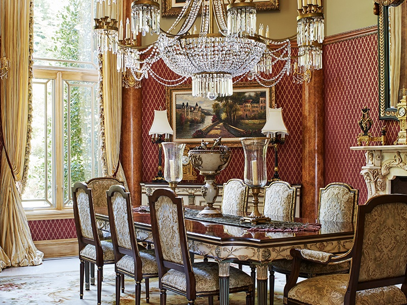 A formal dining room boasts columns that are two-stories high and topped with old leaf.