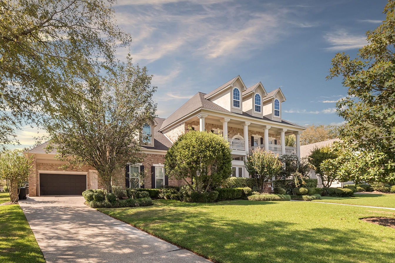 This elegant brick mansion in Lake Conroe pays homage to the Southern Colonial architectural style.