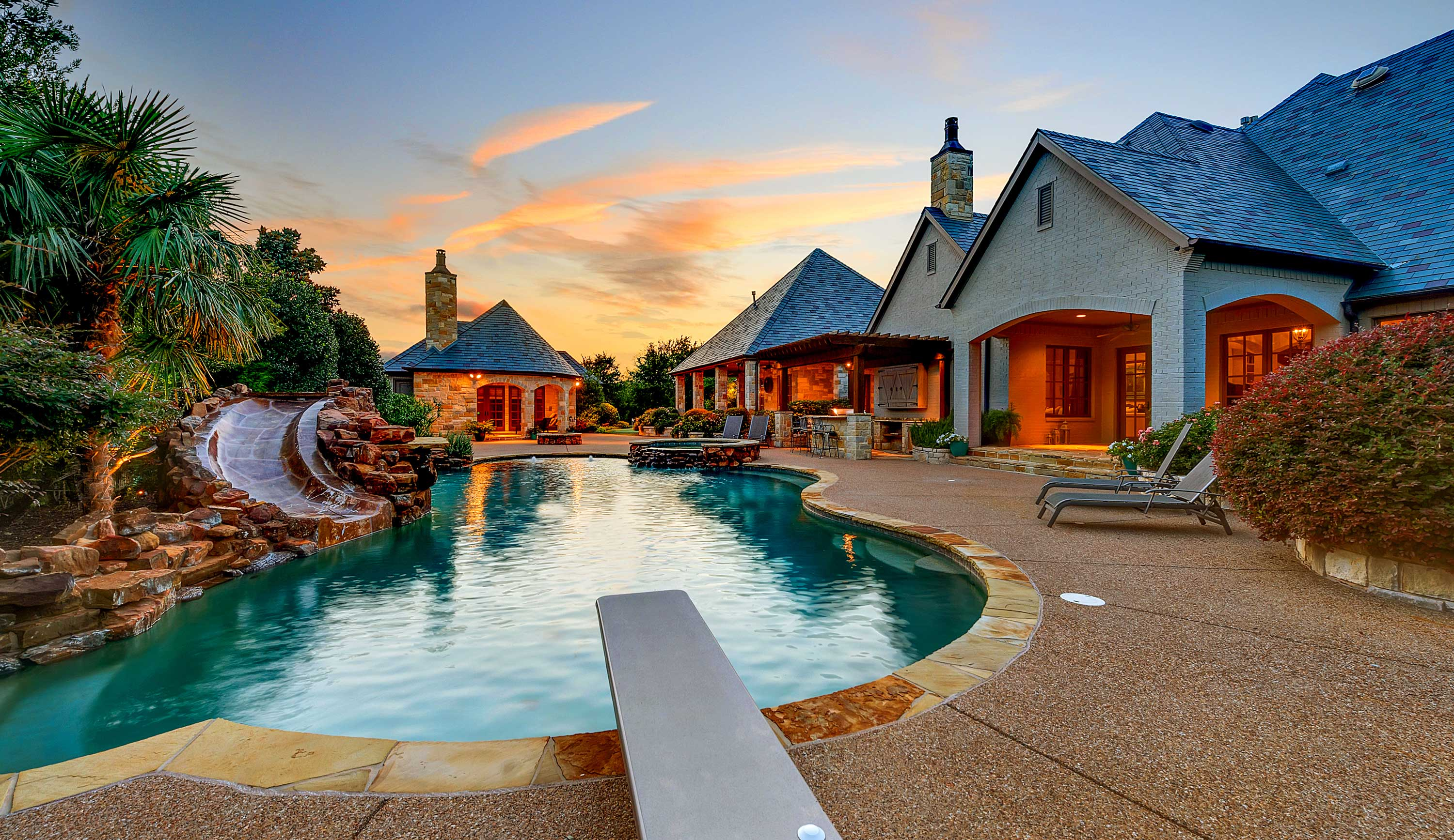 At this Texas home, a resort-style pool with a waterslide and diving board, a media room, game room, and craft room provide year-round entertainment for children.
