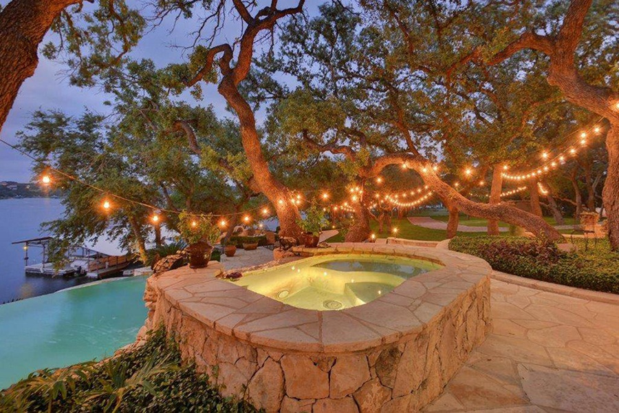 This stone spa cascading into an infinity pool is just one of two hot tubs that overlook the lake along this Hill Country home's shaded waterfront.