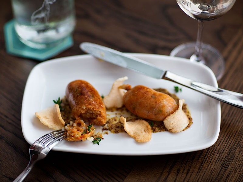 """Visitors to The Grey can expect """"a combination of great service and really good food,"""" such as one of Mashama Bailey's signature dishes, Seafood Boudin. The menu also features Dirty Duck Rice and Stuffed Cherrystone Clams."""