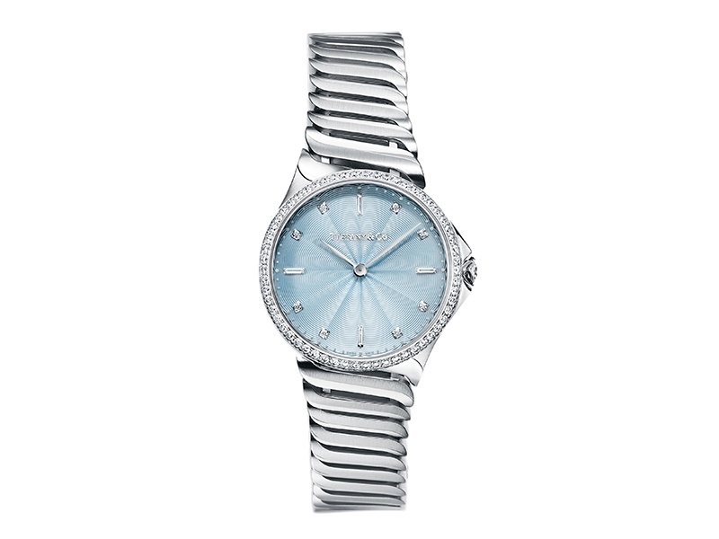 Tiffany & Co's Metro collection features watches in a variety of styles and colors. In this version, the case is set with round brilliant diamonds, and the dial is a lacquered ice-blue color with flinqué finishing. Every watch has a serialized diamond on the crown.