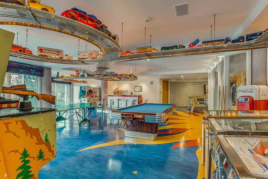 The colorful arcade room in this unique Toronto residence enjoys plenty of natural light and has its own 1950s-style soda bar