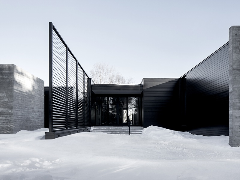 The metal and glass exterior of Alain Carle Architecte's True North residence, in rural Ontario, Canada, reflects light and creates shadows so the appearance of the building constantly shifts and reshapes.