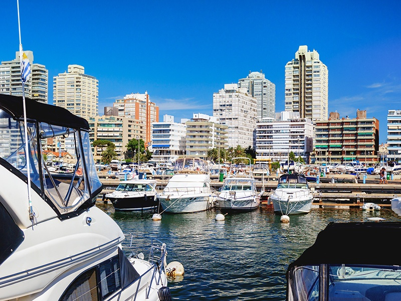Yachts line the marina at Punta del Este against a backdrop of skyscraper apartment blocks. Banner image: Yellow stucco house in Colonia del Sacramento. Photographs: Getty Images