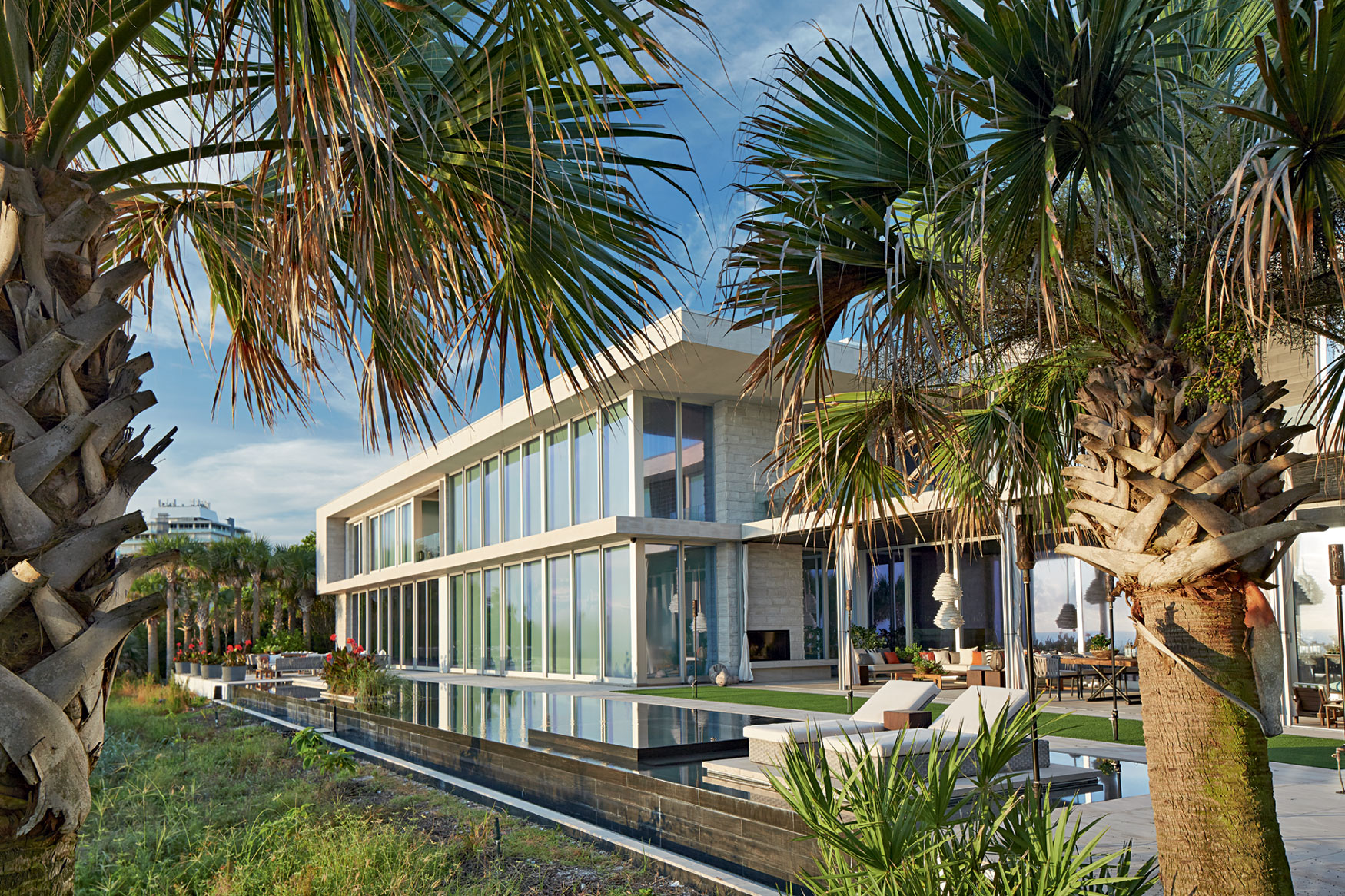 The main home is arranged around a double-height great room, with a vast expanse of glass connecting the space to the pool terrace and ocean views.