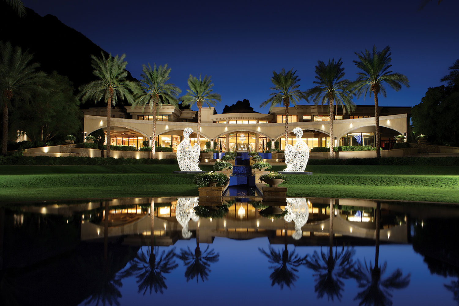 A pair of illuminated sculptures, sitting astride a central waterway, guard the entrance to Villa Paradiso, an estate of unmatched grandeur in Arizona's Paradise Valley.