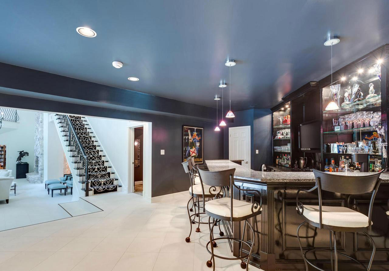 This designer home has a stellar lineup of amenities; in addition to a contemporary screening room, there is a cocktail lounge, catering kitchen, game room, tropical pool area, and tennis court, offering a unique resort experience just 20 minutes outside Washington, DC.