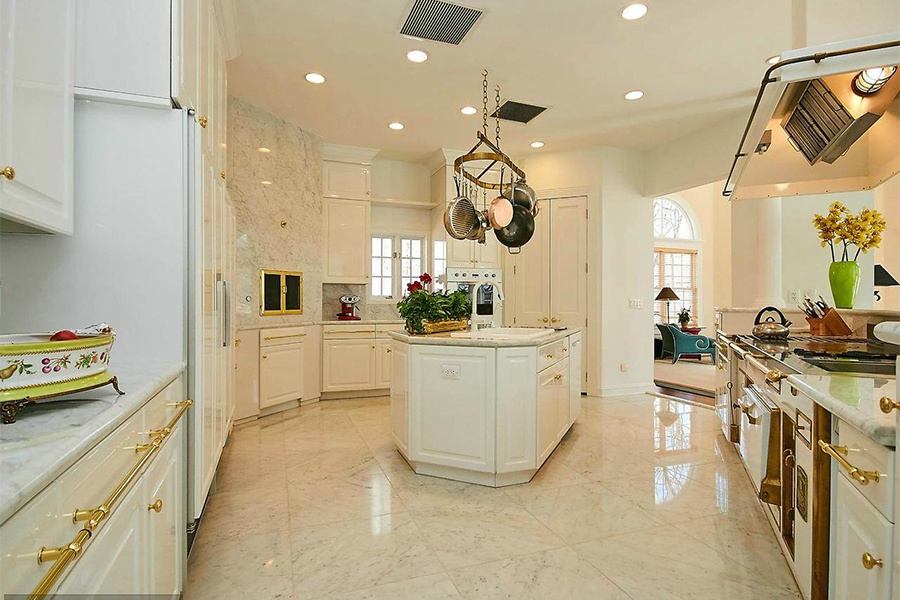 With its marble finishes, elegant brass fittings, and impressive appliances, the kitchen in this Washington, D.C.-area home is the perfect place to prep for a party.