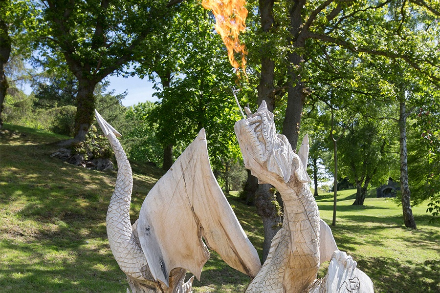 Rising from a tree stump, this custom-carved wooden dragon bears the castle's coat of arms—repeated on the dining room chairs and over a fireplace within—and breathes fire as visitors pass by.