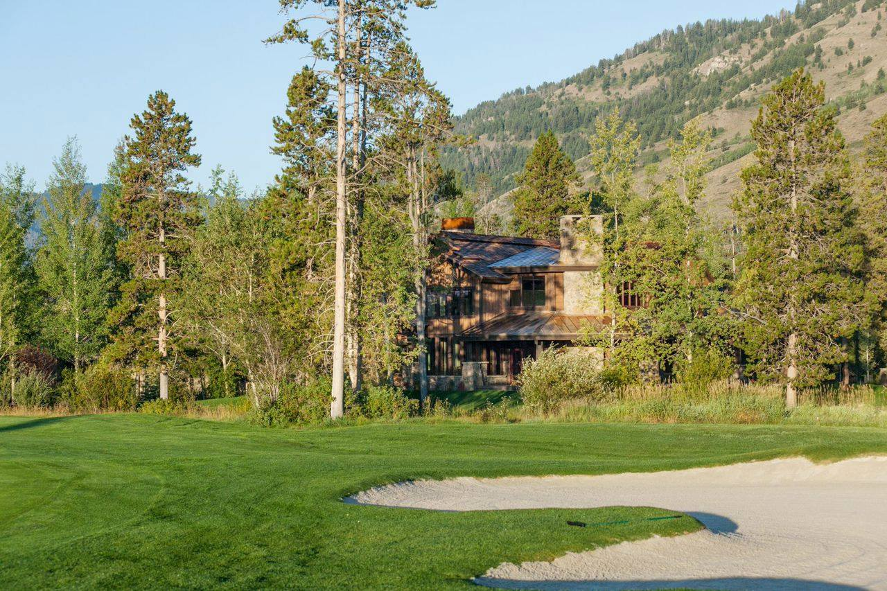 This five bedroom estates features sunny open views of the golf course and views of the Tetons, two master bedroom suites each with its own fireplace, an open floor plan with a soaring great room and kitchen overlooked by a 2nd story balcony atop the winding staircase, and an elevator.