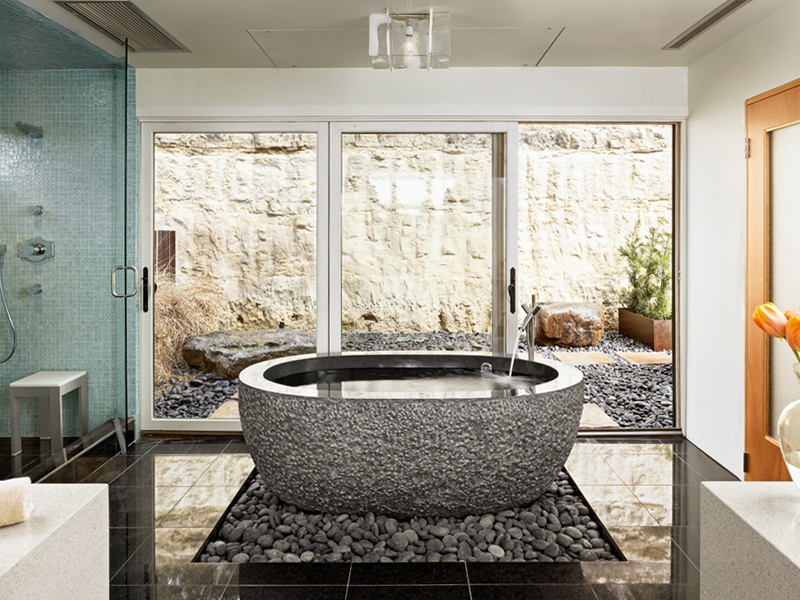 Winn Wittman Architecture provides interior design expertise to select fixtures and finishes that work in harmony with the home. Pictured is an award-winning bath at Soaring Wings, featuring a granite tub and river rocks.