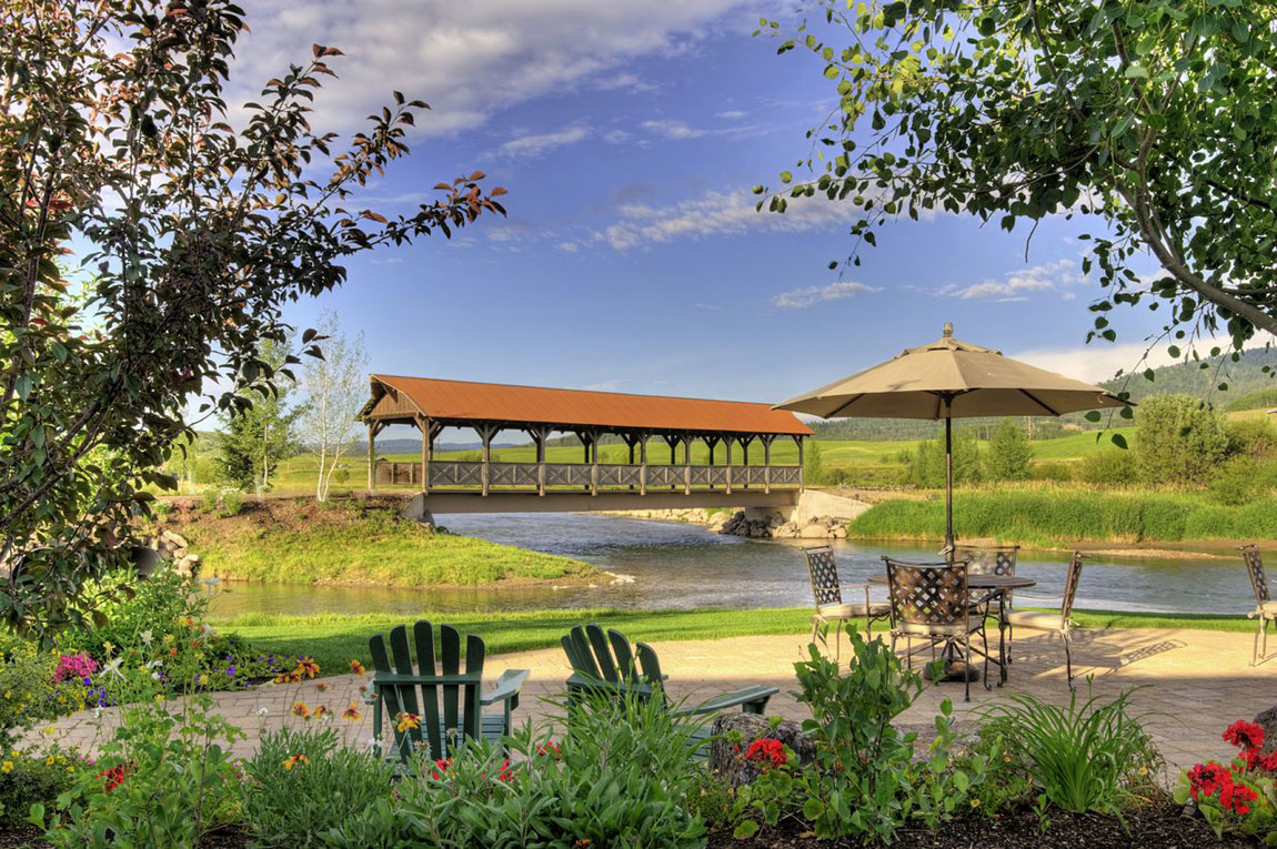 The view from one of the home's entertaining terraces overlooks the river and a charming covered bridge.
