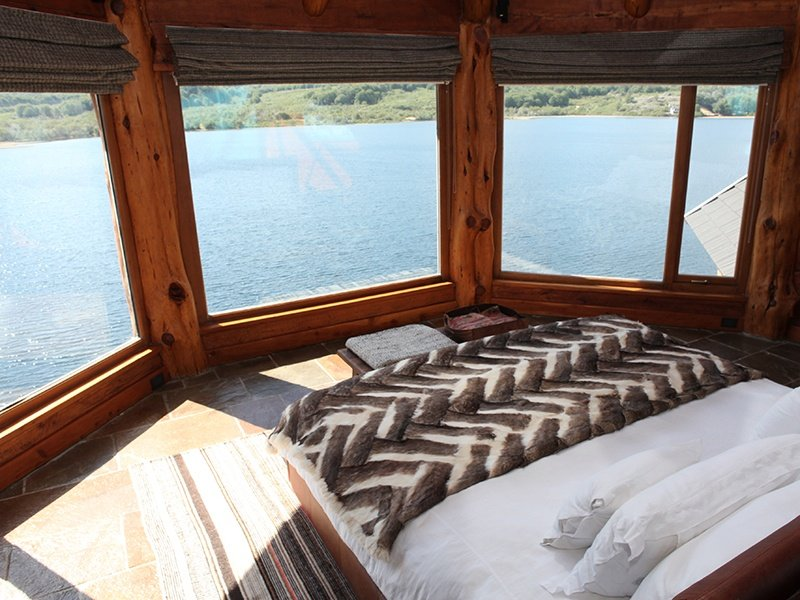 Views from the handsomely outfitted interior rooms look over the shimmering lake and towards the mountains beyond.