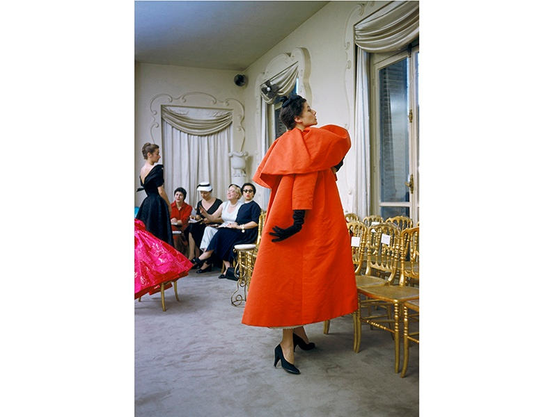 A model wears an orange Balenciaga coat as I. Magnin buyers inspect a dinner outfit in the background in Paris, 1954. <i>Balenciaga: Shaping Fashion</i>, sponsored by American Express, is at the V&amp;A until February 18, 2018. Photograph: © Mark Shaw/mptvimages.com