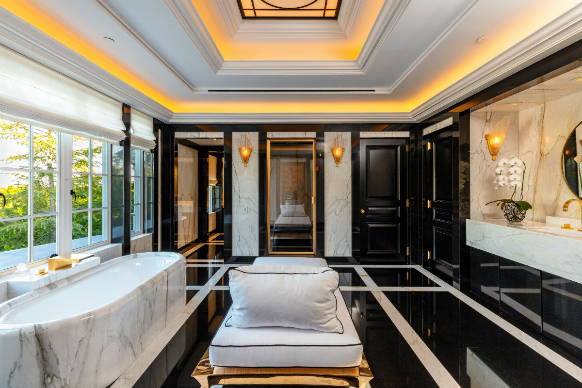 A lavish master bath is resplendent with marble and granite surfaces as well as recessed lighting.