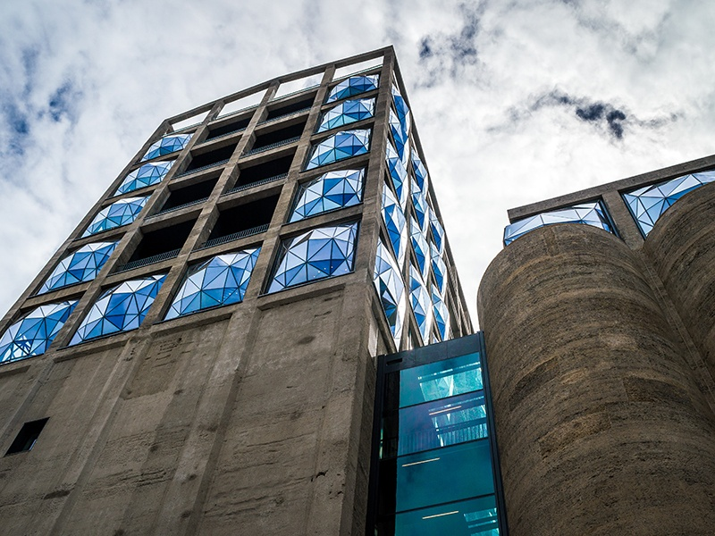 The Silo occupies six floors above the Zeitz Museum of Contemporary Art Africa. Designed by Heatherwick Studio, the building is punctuated with geodesic windows protruding from the concrete structure. Photograph: Getty Images. Banner image: The lobby of The Schaller Studio hotel in Bendigo, Australia, part of the Art Series Hotel Group, with a detail from Mark Schaller's vibrant <i>Port Phillip Bay, Red</i> (2011).