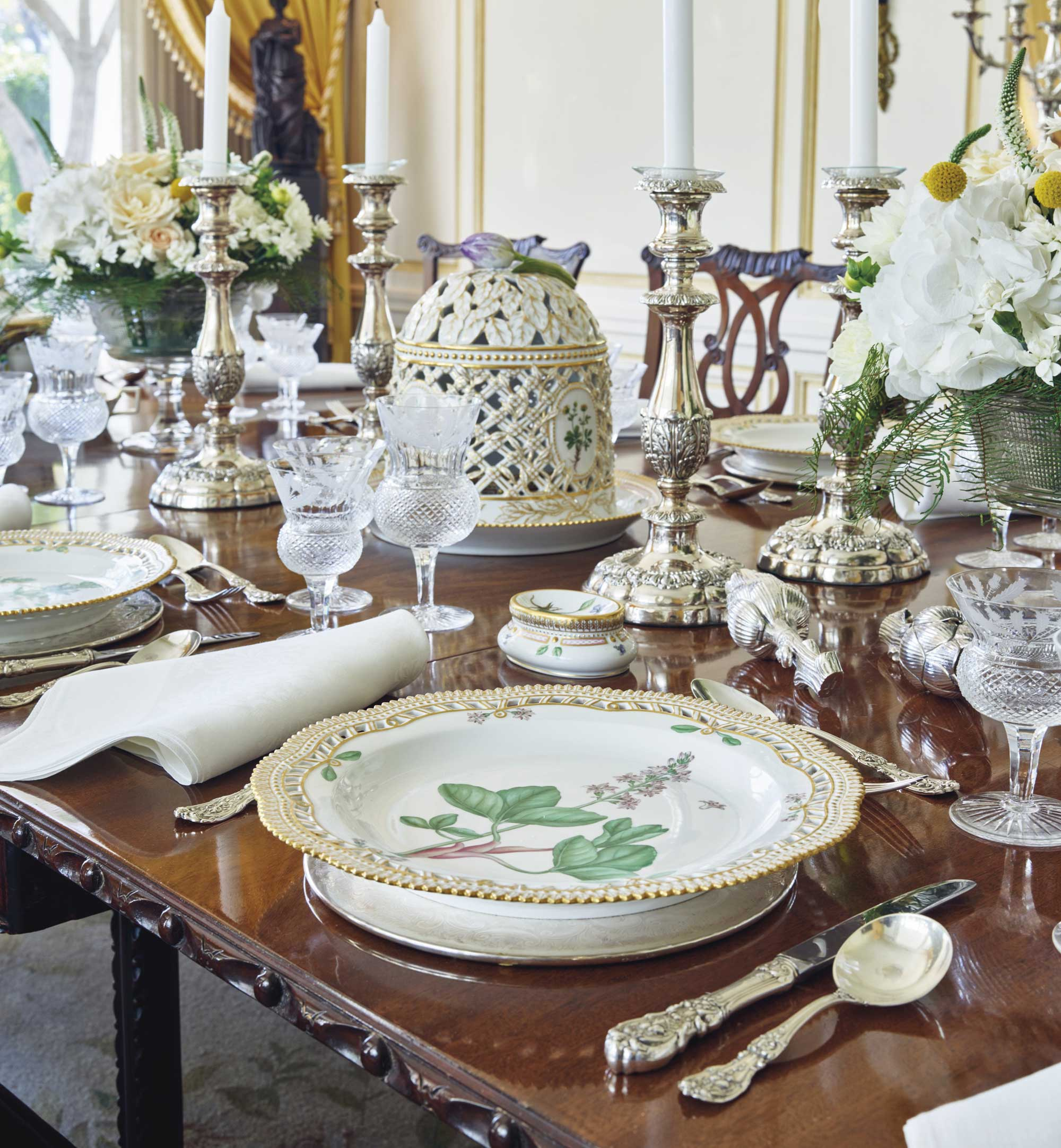 The dining room at Mrs. Bloomingdale's Hollywood Regency villa, featuring the Early George III Mahogany Gate-Leg Dining Table with the 'Flora Danica' Part Dinner Service.