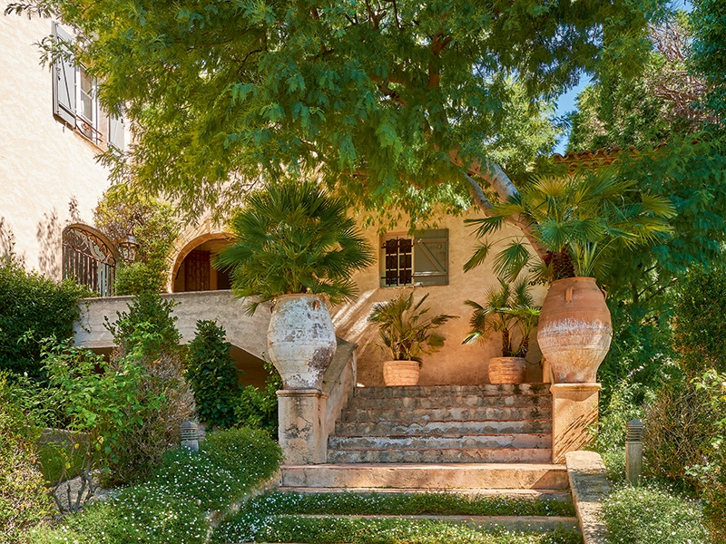 A charming staircase, inset with flowers and bordered by well-kept hedging, leads to the stone archway of the entrance of the property. Photograph: Frederic Vasseur