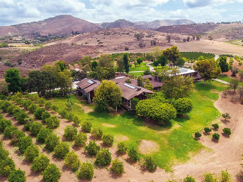 Del Dios Ranch, within Rancho Santa Fe north of San Diego, California, comprises some 210 acres. The residence is a magnificent redwood, glass, and concrete structure, and the property features a lake, tennis court, and equestrian facilities. On the market for $85,000,000 with Willis Allen Real Estate.