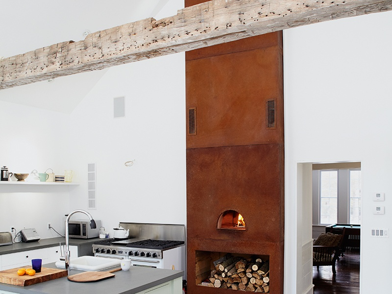 Original beams and hardwood floors from the original property were exposed during renovation of the Floating Farmhouse, with a wood-burning stove added to the kitchen. Photograph: Mark Mahaney