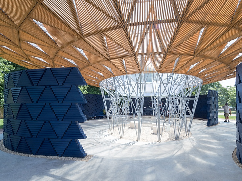 Each of the steel poles supporting the Serpentine Pavilion 2017's timber roof is angled slightly differently to create the ellipse at its center. Photograph: ©2017 Iwan Baan