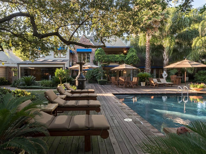 The backyard of this home is customized with a resort-style pool, wet bar, tennis court, and covered lounging area, in addition to the golf course. Photograph: Nan and Company Properties