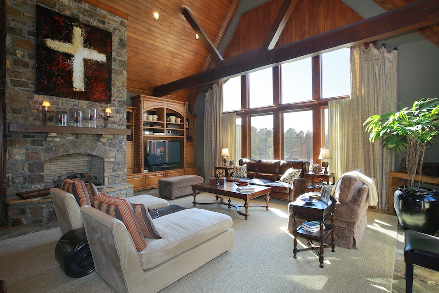 The majestic great room has a double-height, wood-paneled ceiling, extra-large windows affording spectacular views of the estate's grounds, and a handsome stone fireplace.