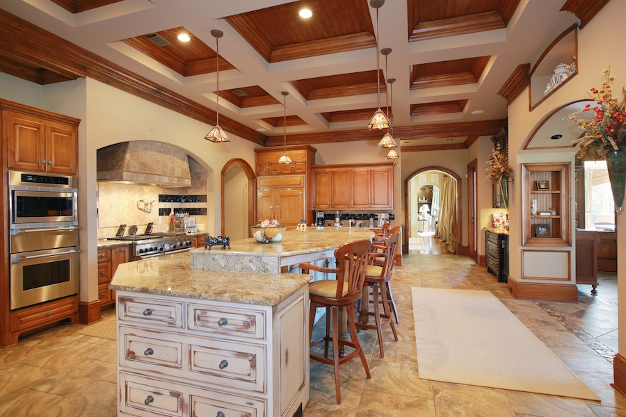The French country-style gourmet kitchen is both state of the art and inviting with a large island and room for a dining table.