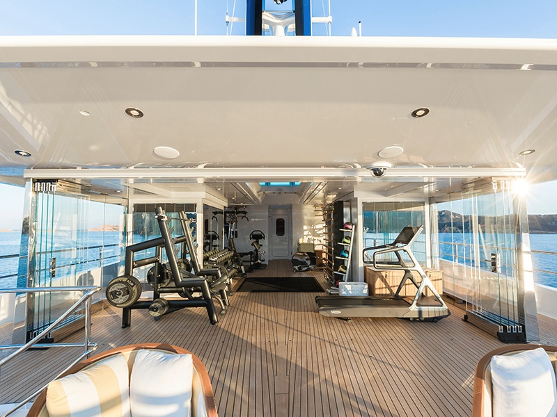Even the glass-walled exercise room on <i>Joy</i> provides a generous outlook of the sea beyond.