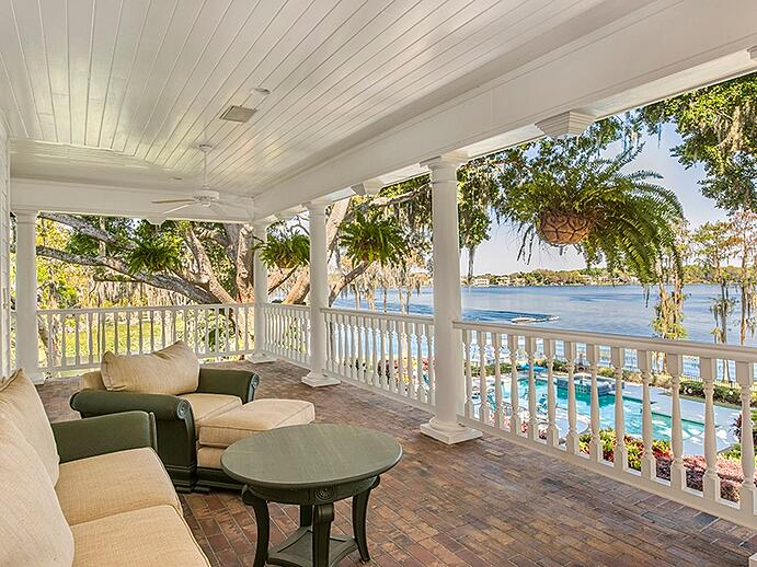 The manor's veranda offers commanding views of the gardens, pool area, and lake. Photograph: Regal Real Estate Professionals