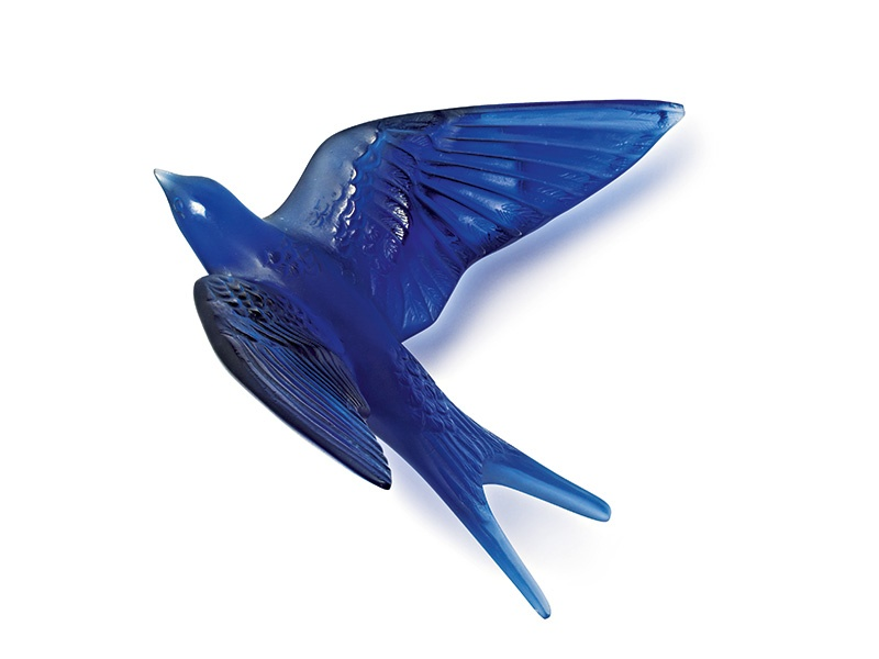 Lalique's swallow wall sculpture in sapphire blue crystal pays tribute to founder René Lalique, who used the swallow motif in many of his jewels and decorative objects.