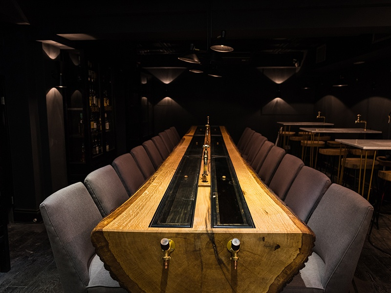 """Abandoning the concept of a traditional bar, Black Rock is lined with glass-fronted whiskey cabinets, and a split oak tree serves as a central table and """"cask"""" for aging two types of whiskey. Photograph: Addie Chinn"""