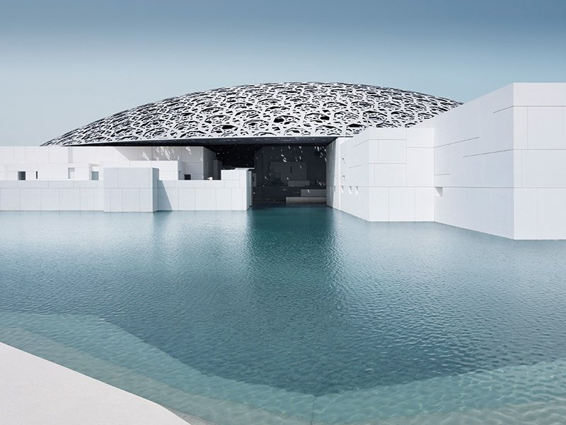 The dome atop the Louvre in Abu Dhabi is constructed from layered aluminum and stainless-steel honeycomb shapes that filter the sunlight into patterned shards that hit the white granite on the walls and floor of the cube-shaped museum buildings. Photograph: ©Louvre Abu Dhabi/Mohamed Somji