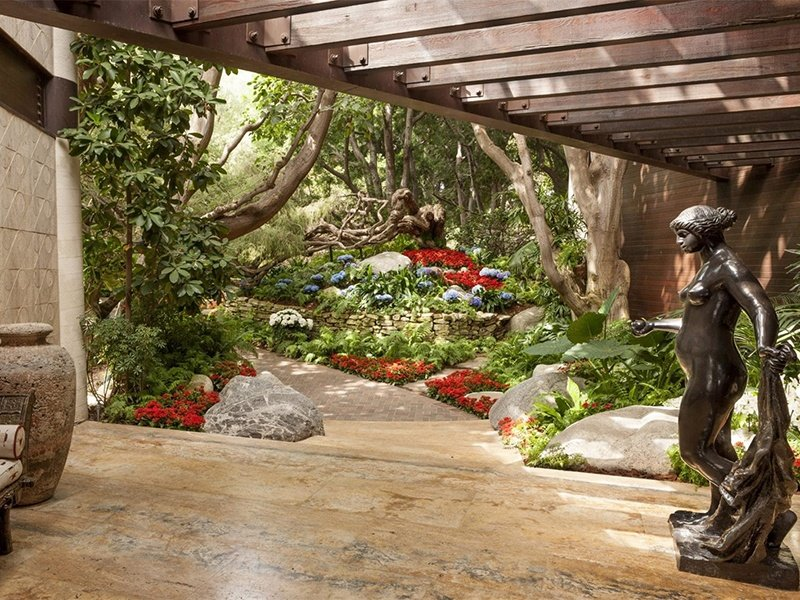 This pristine home in Malibu, California has four acres of thriving grounds, a canopy of specimen trees, and an indoor arboretum.