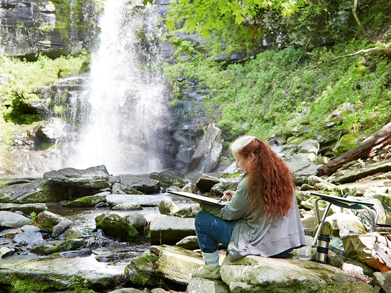Mariella Bisson, photographed at the base of Plattekill Falls as she works on a watercolor painting (<i>seen below</i>). Photograph: Laura Moss. Banner image: The field painting <i>Waterfall, Ochre Rocks</i> (2014) captures the falls in Willoughby State Forest in Vermont—Mariella Bisson's home state.