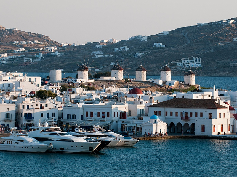 The windmills of Mykonos tower over Chora, looking down to the sea and out to the yacht-filled marina. Photograph: Alamy