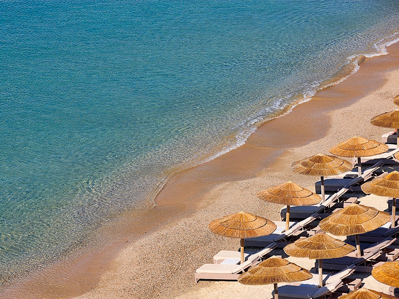Elia beach—with its golden sands and clear waters—stretches below several of the Myconian Collection hotels, with a section of lounges and umbrellas reserved for guests.
