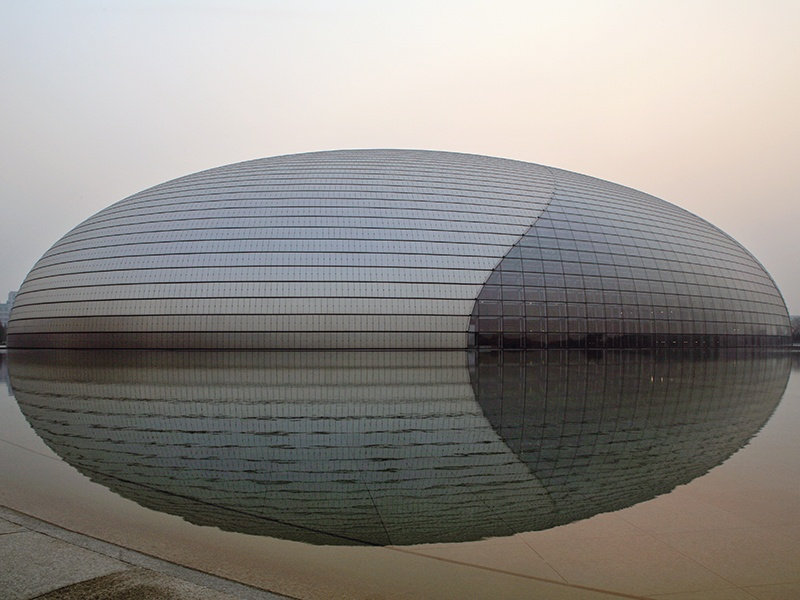 """Completed in 2007, Paul Andreu's National Centre for the Performing Arts in Beijing is set at the heart of a man-made lake. A literal """"cultural island,"""" it encompasses an opera house, concert hall, and two theaters within its titanium and glass shell. Photograph: Paul Maurer"""