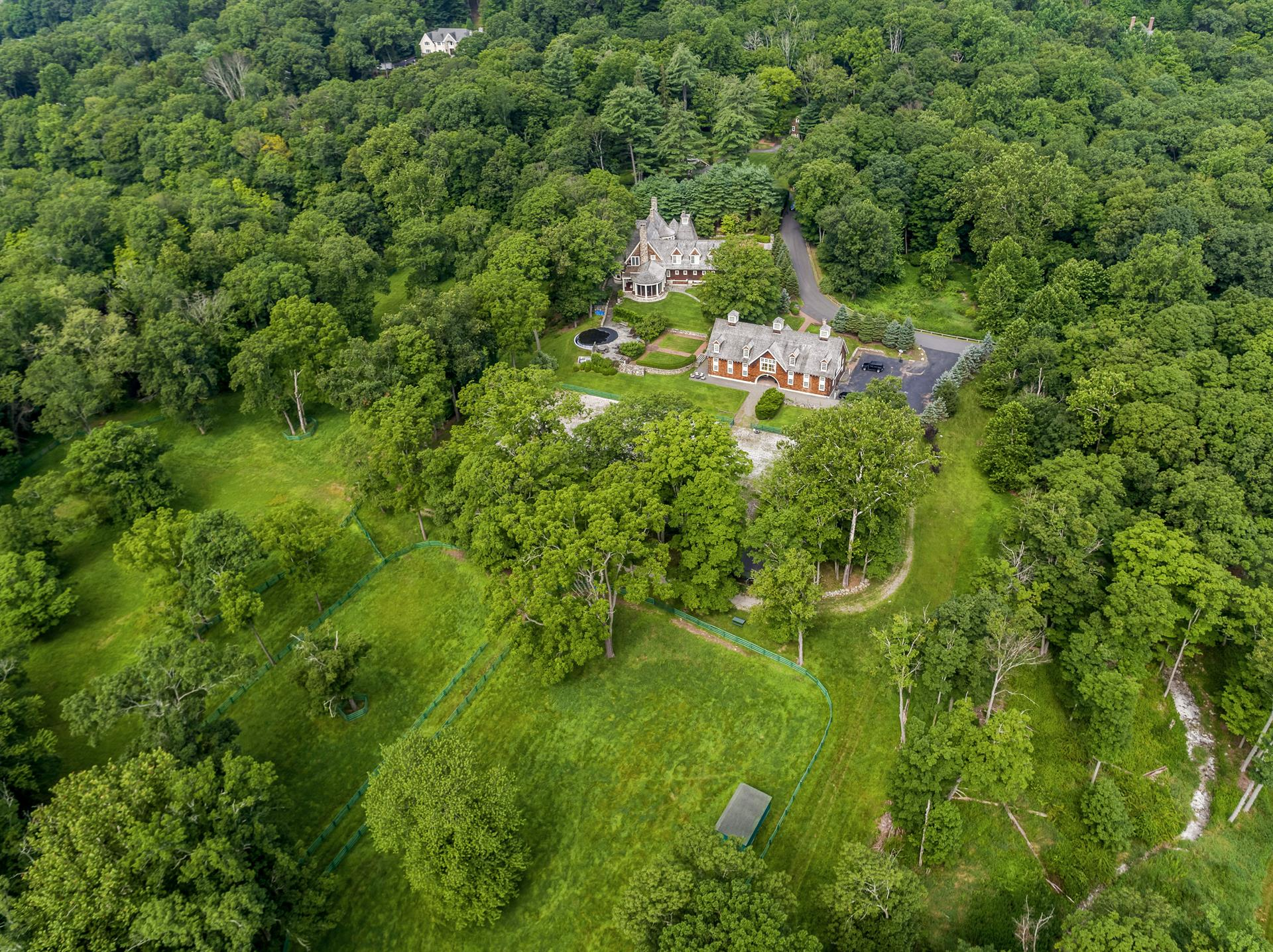 This riverfront estate's outstanding amenities include a nine-stall barn, jumping area, paddocks, and riding trails along New Jersey's Ramapo River.