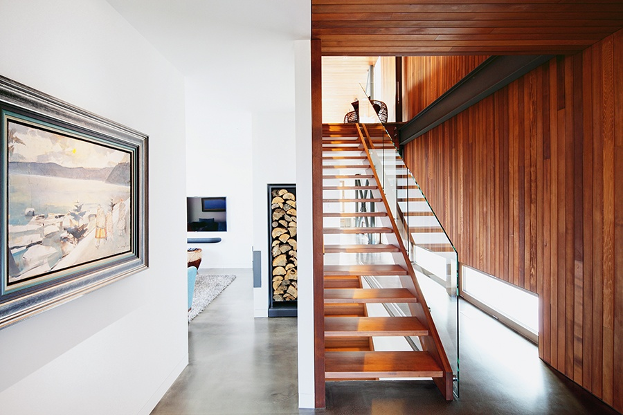 Red cedar accents on the stairs, walls, and ceilings add warmth to the minimalist interiors. Photograph: Alexandre Guilbeault