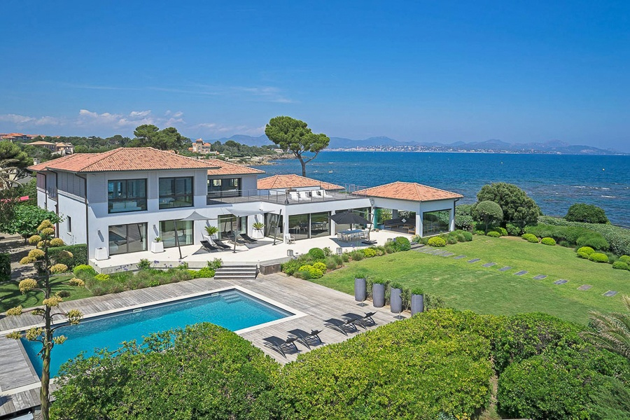 This secluded estate in Saint Aygulf, Var comprises a villa and two guest houses on a picturesque stretch of shoreline. This seven-bedroom home also has a heated pool, a helipad, and beach access.