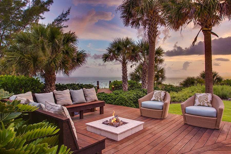 Fire elements provide warmth and enhance the ambiance of the outdoor living room of this luxury home in Nokomis, Florida.