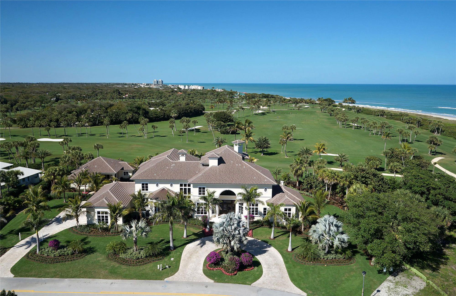 Completed in 2014, the luxurious estate includes a three-story, 14,997-square-foot main house, a separate guest house, and beautifully landscaped grounds. The property boasts panoramic views of emerald fairways and aquamarine waters.