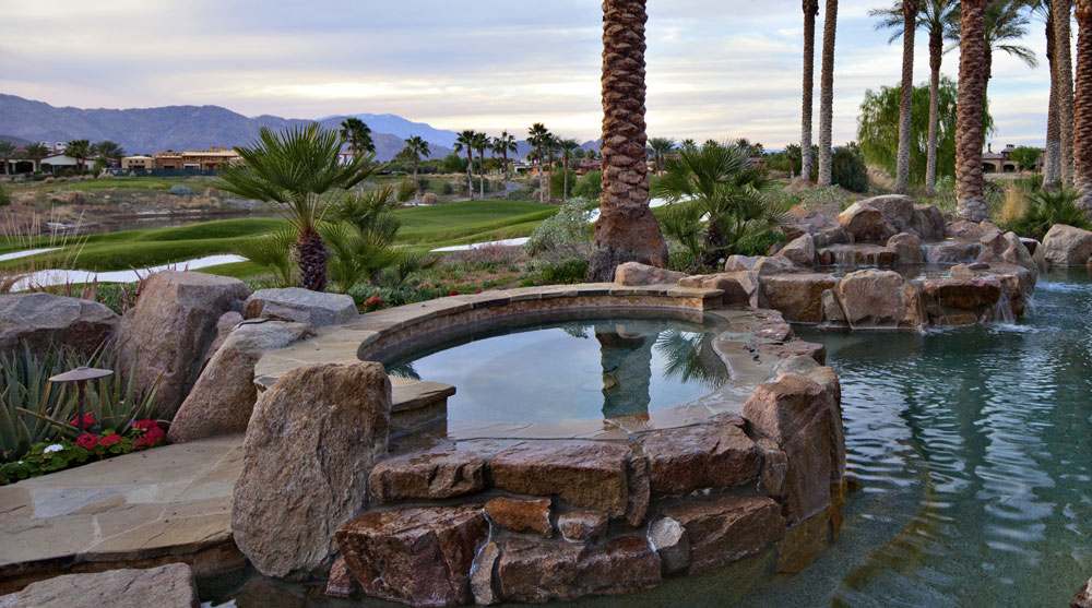 A fabulous outdoor living area features a stone fireplace, custom pool with stone built water falls, ponds and a raised spa, all overlooking the greens.