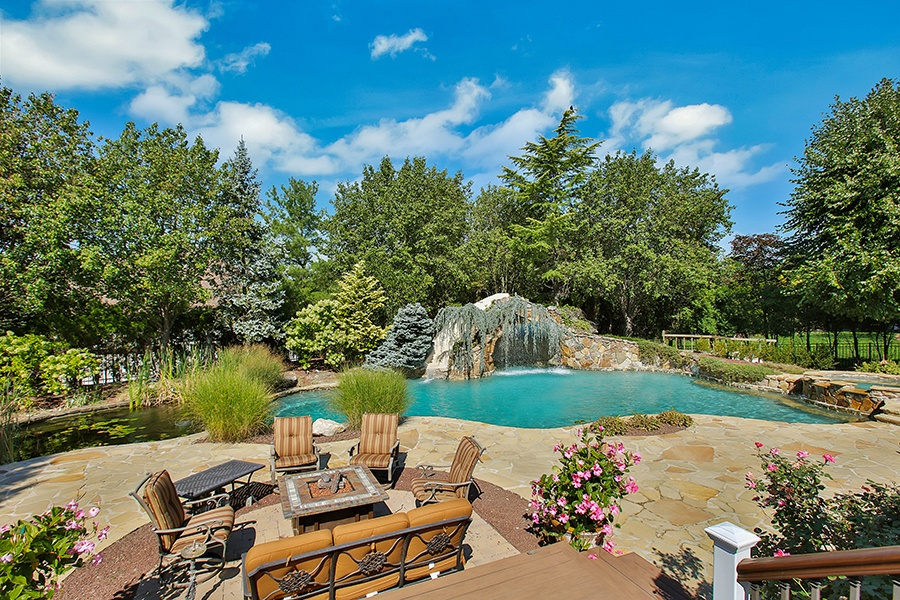 Featuring a cascading waterfall, natural rock work, and landscaping evocative of a forest, this stunning pool at an estate in Holmdel, New Jersey, characterizes the natural-pool trend.
