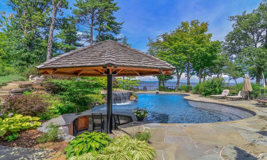 Naturalistic landscaping combined with a breathtaking lake view give the pool-side bar of this Canadian estate a tropical feel.